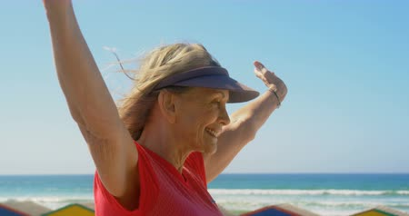 senior citizen : Side view of active senior Caucasian woman standing on a promenade at beach. She is smiling and looking at camera 4k