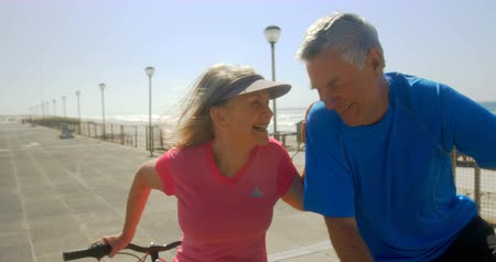 уик энд : Front view of active senior Caucasian couple interacting with each other on a promenade at beach. They are standing with their bicycle 4k