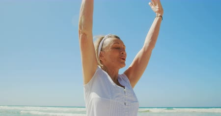 kapalı : Front view of active senior Caucasian woman performing yoga on the beach. She is meditating with eyes closed 4k