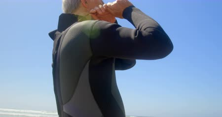 active ageing : Low angle view of active senior Caucasian male surfer wearing wet suit on the beach. He is getting ready for surfing 4k