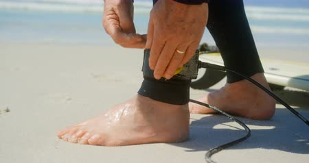 yalınayak : Low section of active senior Caucasian male surfer tying surfboard leash on her leg on the beach. She is getting ready for surfing 4k