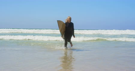 sports suit : Front view of active senior Caucasian female surfer running on sea in the sunshine. She is holding surfboard 4k