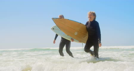 teljes hosszúságú : Front view of active senior Caucasian couple running on the sea at beach. They are holding surfboard 4k