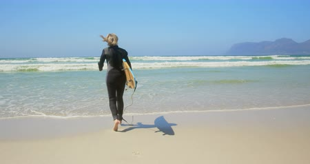 teljes hosszúságú : Rear view of active senior Caucasian female surfer running on sea in the sunshine. She is holding surfboard 4k