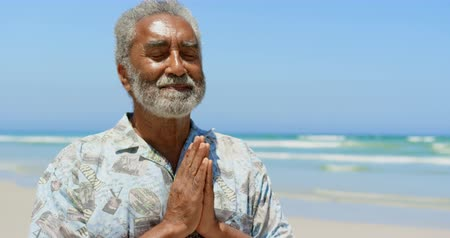 голова и плечи : Front view of active senior African American man performing yoga on the beach. He is meditating with eye closed 4k Стоковые видеозаписи