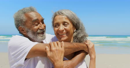 голова и плечи : Front view of happy active senior African American man embracing senior woman on the beach. They are talking with each other 4k