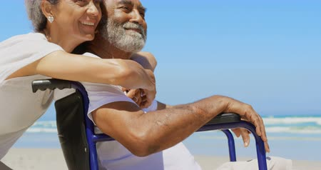 emeryt : Side view of active senior African American woman embracing disabled senior man on the beach. They are smiling and looking at sea 4k