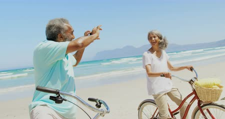 fotografando : Side view of active senior African American man taking photo of woman with mobile phone at beach. They are standing with bicycle in the sunshine 4k