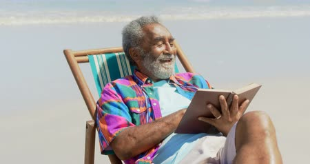 пенсионер : Front view of active senior African American man reading a book on deckchair at beach. He is smiling 4k Стоковые видеозаписи