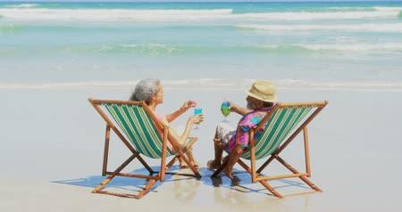 cappello di paglia : Rear view of active senior African American couple toasting drinks on deckchair at beach. They are sipping drinks 4k
