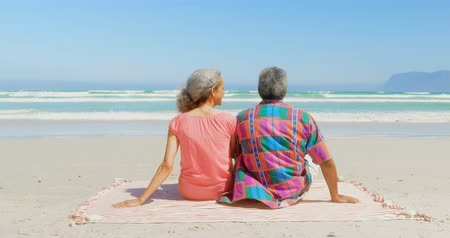 emekli : Rear view of active senior African American couple relaxing on blanket in the sunshine at beach. They are talking with each other 4k