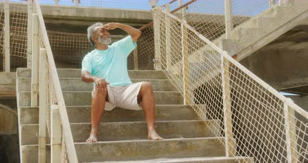 merdiven : Front view of active senior African American man with shielding eye sitting on stair at promenade. He is smiling and looking away 4k Stok Video
