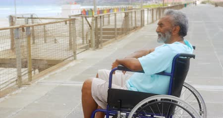 пенсионер : Side view of thoughtful disabled active senior African American man in wheelchair on promenade. He is looking away 4k Стоковые видеозаписи