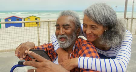 rokkant : Front view of active senior African American couple taking selfie with mobile phone on promenade. Senior woman embracing and kissing him on cheek 4k Stock mozgókép