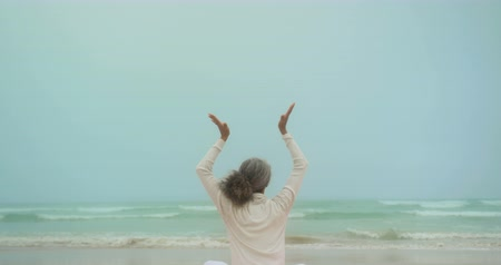 clasped : Rear view of active senior African American woman doing yoga on exercise mat at the beach. She is meditating 4k Stock Footage