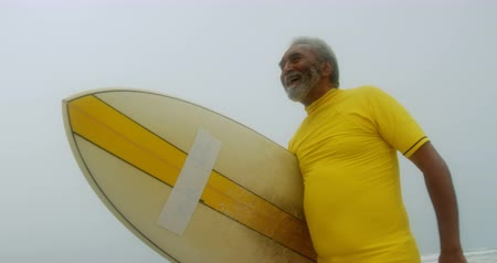 baixo ângulo : Low angle view of active senior African American man with surfboard walking on the beach. He is smiling 4k