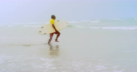 gepensioneerd : Side view of active senior African American male surfer running towards sea on the beach. He is holding surfboard 4k