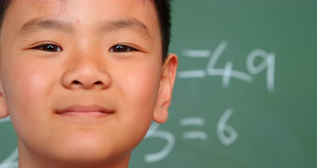 multiplicacion : Close-up of Asian schoolboy standing against chalkboard in a classroom at school. He is smiling and looking at camera 4k