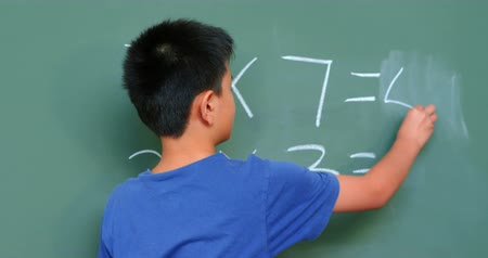 schoolkid : Rear view of Asian schoolboy solving math problem on chalkboard in classroom at school. He is doing multiplication 4k Stock Footage