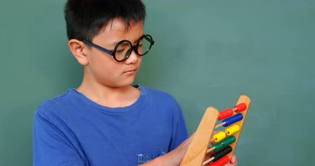 aritmetica : Front view of Asian schoolboy solving math problem with abacus in a classroom at school. He is standing against green chalkboard 4k
