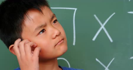 multiplicacion : Front view of thoughtful Asian schoolboy scratching his head against chalkboard in classroom. He is looking away 4k
