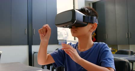 академический : Front view of Asian schoolboy sitting at desk and using virtual reality headset in classroom. He is gesturing 4k