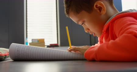 információ : Side view of attentive Asian schoolboy studying at desk in classroom at school. He is writing on notebook 4k