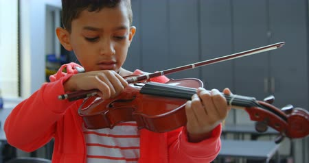 ártatlanság : Front view of attentive Asian schoolboy playing violin in classroom at school. He is learning music 4k Stock mozgókép