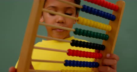 aritmética : Front view of African American schoolboy learning mathematics with abacus in a classroom. He is counting beads 4k