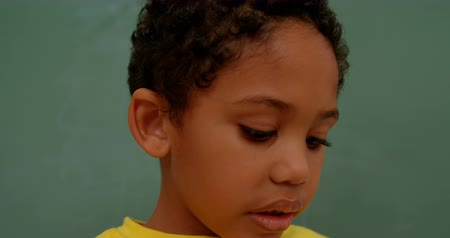 looking down : Close-up of African American schoolboy standing against green chalkboard in classroom at school. He is looking down 4k