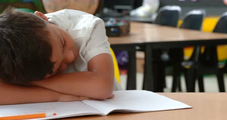 hajló : Front view of Asian schoolboy sleeping on desk in classroom at school. He is leaning on book 4k