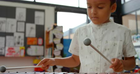 xilofono : Front view of Asian schoolboy playing xylophone in a classroom at school. He is learning music 4k Filmati Stock