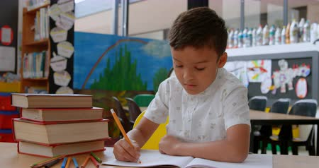 ártatlanság : Front view of Asian schoolboy raising hand while studying on desk in classroom at school. He is writing on notebook 4k Stock mozgókép