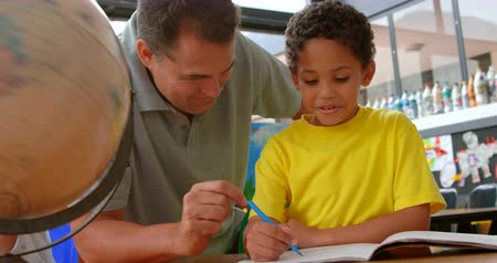 ártatlanság : Front view of young Caucasian male teacher teaching African American schoolboy in classroom. They are sitting at desk 4k Stock mozgókép