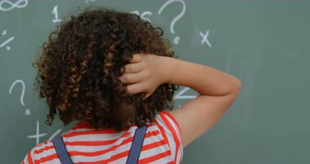 résoudre : Rear view of mixed-race schoolgirl scratching her head in classroom at school. She is solving math problem 4k Vidéos Libres De Droits