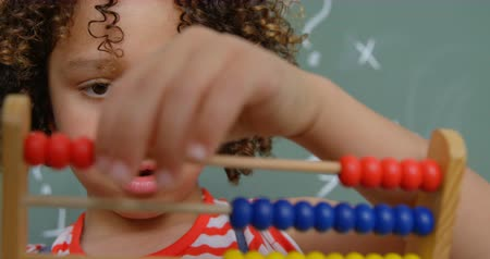 aritmética : Front view of mixed-race schoolgirl learning mathematics with abacus in a classroom at school. She is counting beads 4k Stock Footage