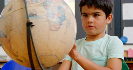 descobrir : Front view of Caucasian schoolboy studying globe at desk in classroom at school. He is looking and spinning globe 4k