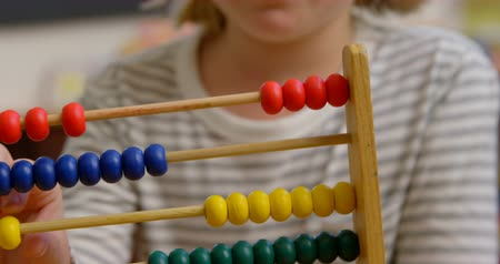 aritmética : Front view of Caucasian schoolgirl learning mathematics with abacus in the classroom. She is counting beads 4k