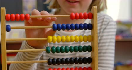 aritmética : Mid section of Caucasian schoolgirl learning mathematics with abacus in the classroom. She is counting beads 4k