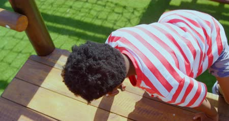 bouldering : Rear view of African American schoolboy playing in school playground on a sunny day. He is climbing a wall 4k
