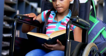 rokkant : Front view of disabled African American schoolgirl reading a book in library at school. She is sitting on wheelchair 4k