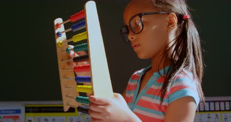 aritmética : Side view of African American schoolgirl with spectacle learning math with abacus in classroom. She is counting beads 4k