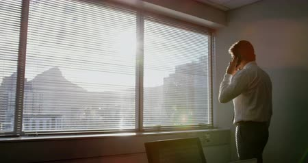 formální : Rear view of young Caucasian male executive talking on mobile phone in a modern office. He is standing near window 4k Dostupné videozáznamy