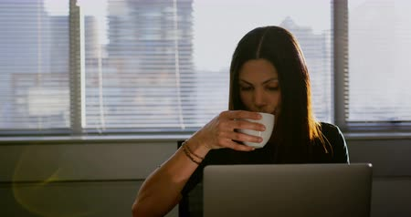 Хорошо одетый : Front view of young Caucasian businesswoman drinking coffee while working on laptop in office. She is sitting at desk 4k