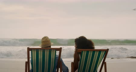 couples : Rear view of African American couple relaxing together on a sun lounger at beach. They are interacting with each other 4k Stock Footage