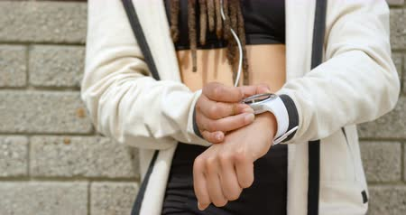 mid section : Mid section of woman using smartwatch in the city. She is leaning against wall 4k