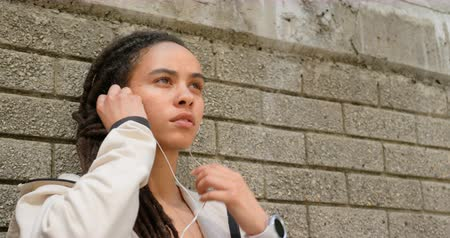 wearing earphones : Front view of young African American woman wearing earphones in the city. She is leaning against wall 4k Stock Footage