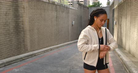 portable information device : Front view of young African American woman using smartwatch in the city. She is listening music 4k