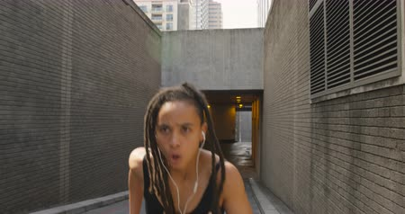 wearing earphones : Front view of African American woman jogging in the city. She is listening music 4k