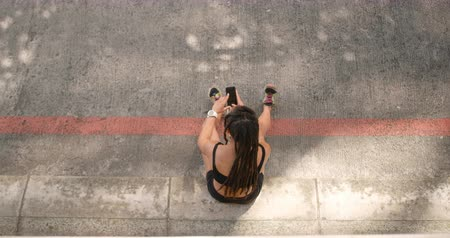 teljes hosszúságú : High angle view of African American woman using mobile phone in the city. She is sitting on the road 4k